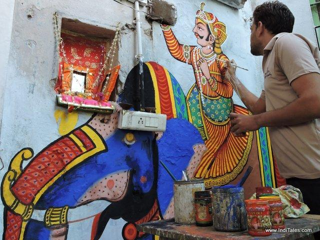 Painter paints the temple walls at Nathdwara