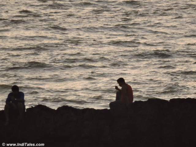 Fishermen on rocks behind Tiracol Fort