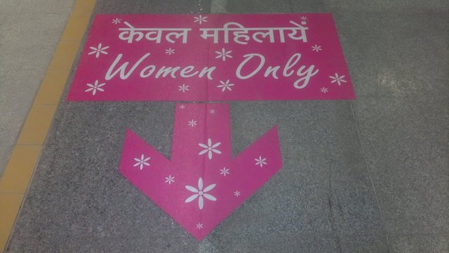 Pink sign guiding towards Delhi Metro's Women Only Coach