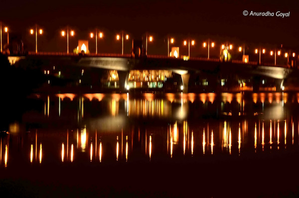 Another bridge lights reflecting in water at night