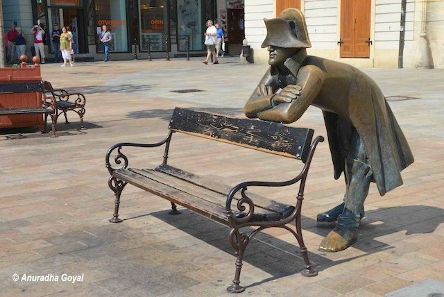 Sculpture of a man leaning on a bench in the city street