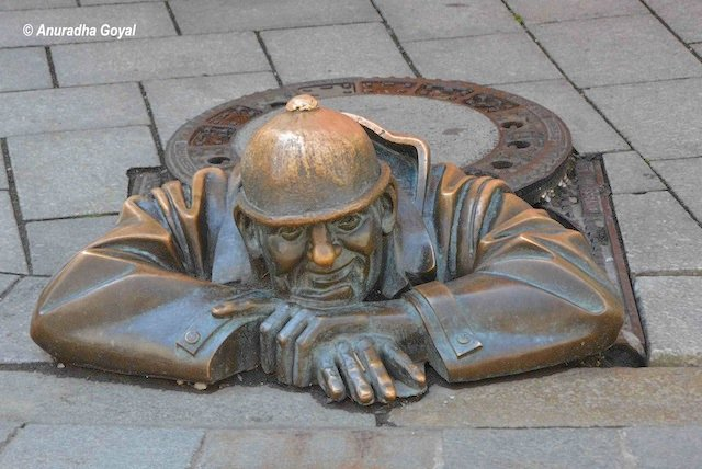 Sculpture of a man standing in drainage at Bratislava