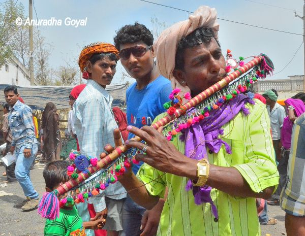 A decorated flute being played at Vaalpur Bhagoria Haat