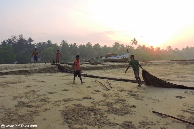 Traditional Fishermen rolling their fishing nets early in the morning