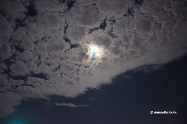 Moon playing hide & seek behind silver colored clouds