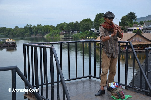 A musician playing flute on the bridge over the River Kwai