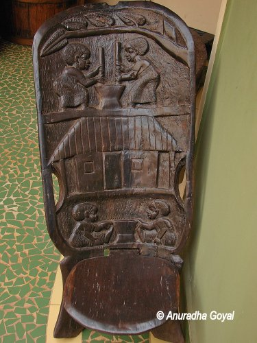 Carvings of women doing daily chores on a wooden chair