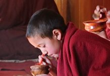 A young monk eating while chanting his morning prayers