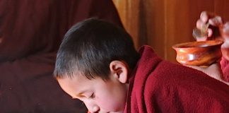 A young monk eating while chanting his morning prayers at Thiksey Monastery Ladakh