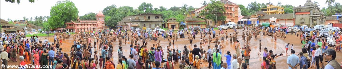 Monsoon Mud Festival ground panoramic view with hundreds of participants and spectators