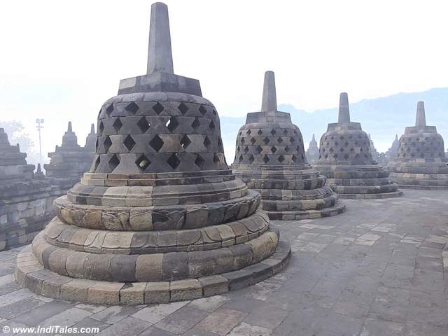 Perforated stupas covering the Buddha Images