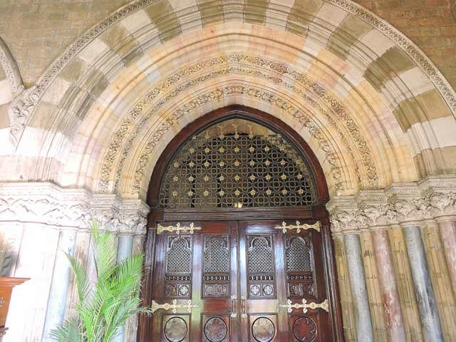 Wooden door framed by recessed arches - CST Mumbai