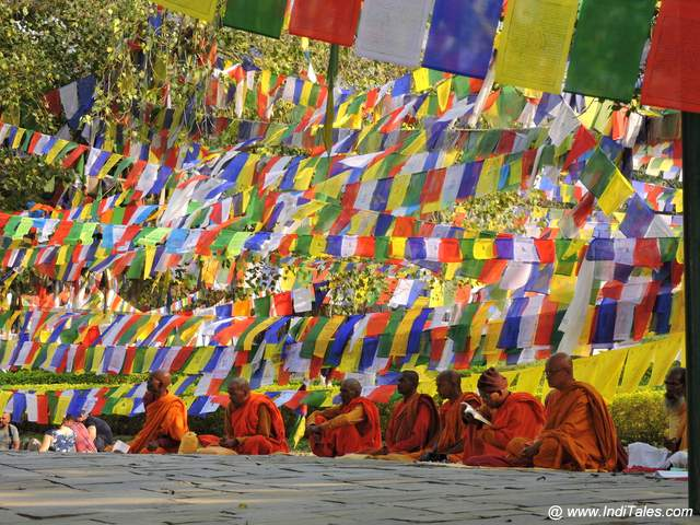 Monks worship under colorful prayer flags at Lumbini Gardens