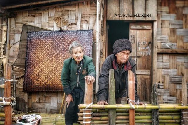 Old Apatani couple sitting outside their home in Ziro Valley