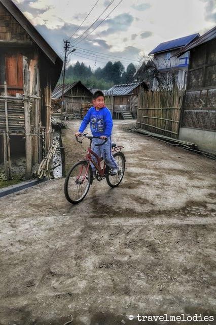 Young Apatani boy cycling around Haji Basti