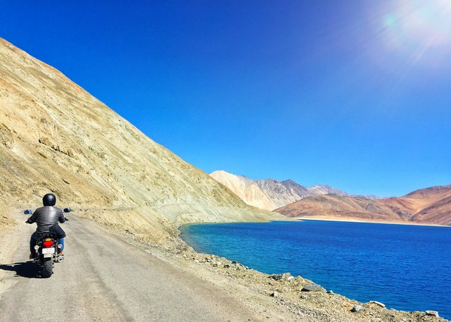Riding a motorbike besides the Himalayan Lake