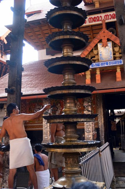 Priest lighting a lamp at Guruvayur Temple