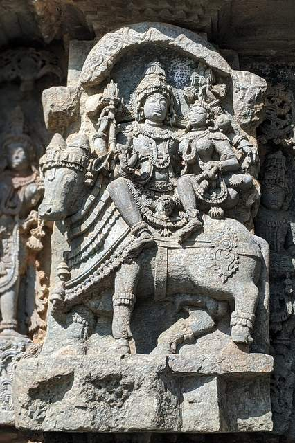 Stone carved sculpture of Lord Shiva and Parvati sitting on Nandi